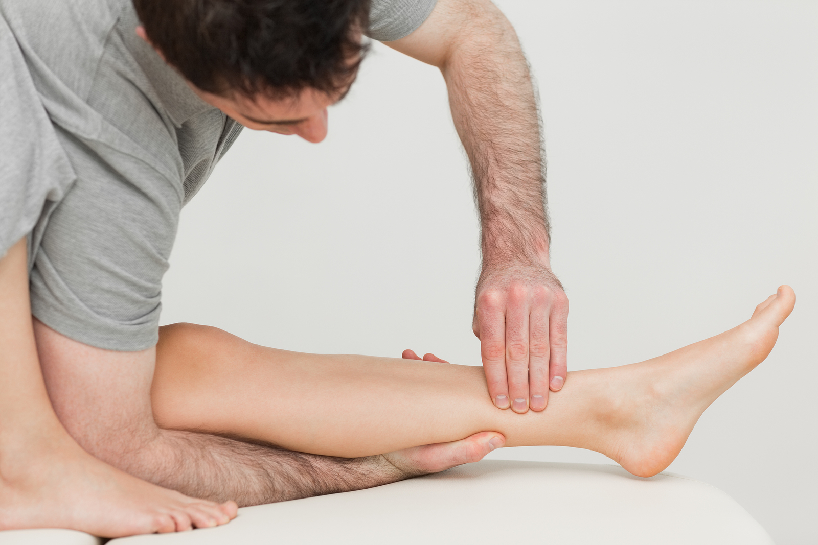 osteopath massaging patient's leg