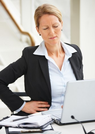 Business woman experiencing back pain.