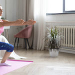 Woman doing squatting exercise in her living room