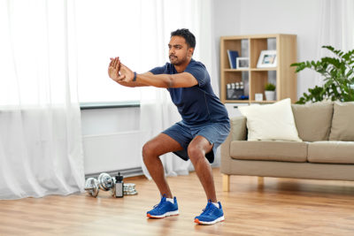 Man doing a squat exercise in his living room
